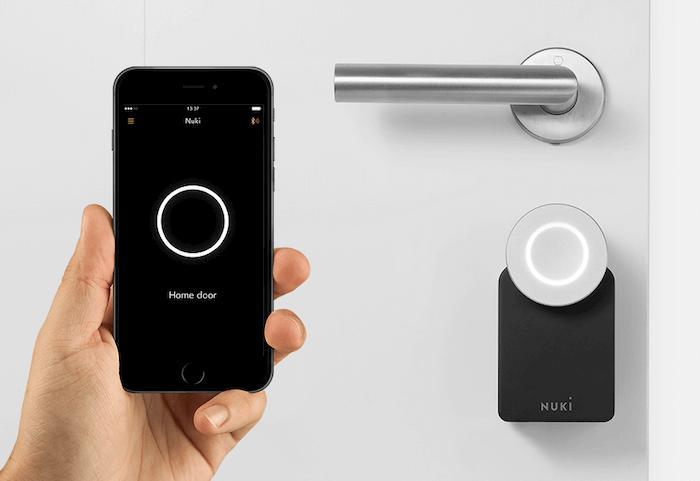 Telefon w dłoni z aplikacją do sterowania zamkiem do drzwi. W tle białe drzwi z elektronicznym zamkiem NUKI.