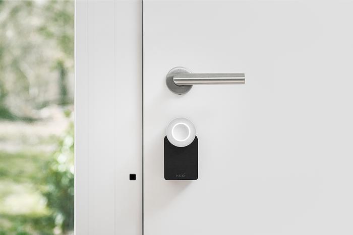 Zamknięte drzwi. Na drzwiach pod klamką elektroniczny zamek NUKI w wersji 2.0. Obok zamka na ościeżnicy przyklejony kontrakton.