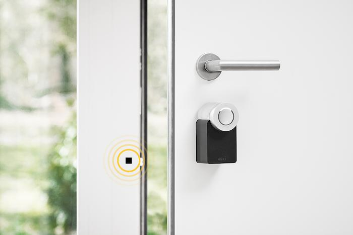 Uchylone drzwi z elektronicznym zamkiem NUKI 2.0 i czujnikiem otwarcia tuż obok zamka na ościeżnicy.