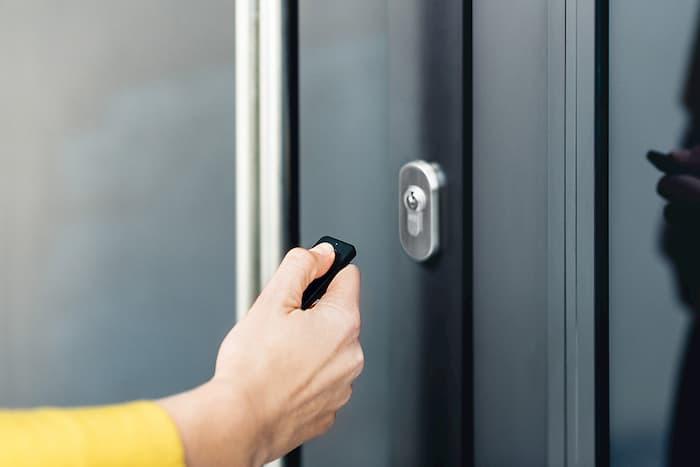 Dłoń wciskająca przycisk na pilocie na wprost drzwi z pochwytem.
