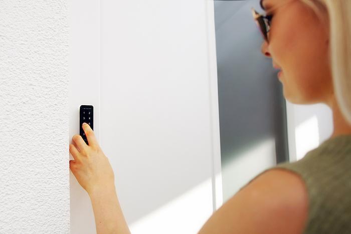 Kobieta wprowadzająca kod PIN do otwarcia drzwi przez elektroniczny zamek.