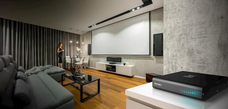 Salon z otwartym ekranem projektora i zasłoniętymi zasłonami. U góry świecą się lightspoty. Po prawej na pierwszym planie centrala Home Center 2 w kolorze czarnym na szafce.