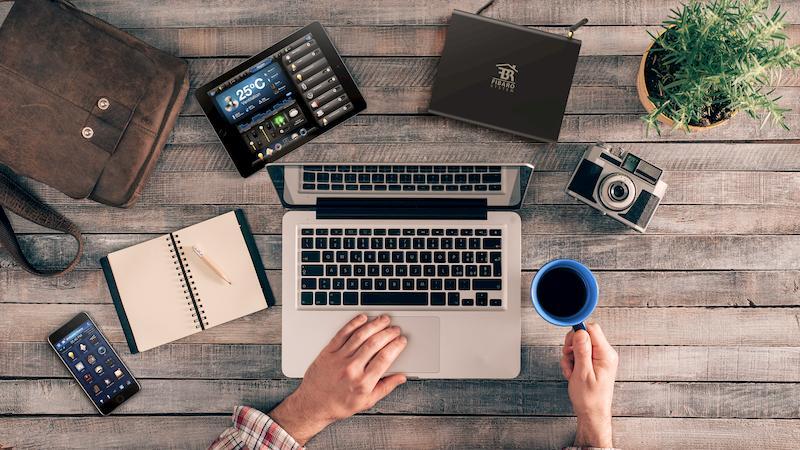 Zdjęcie biurka z góry. Na środku Mac, u góry centrala Home Center 2 i tablet do sterowania systemem automatyki budynkowej Fibaro. Po lewej telefon z włączoną aplikacją fibaro.