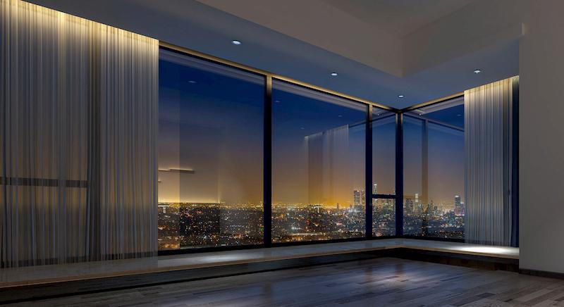 Duże okna narożne z zasłonami zawieszonymi na karniszach elektrycznych.