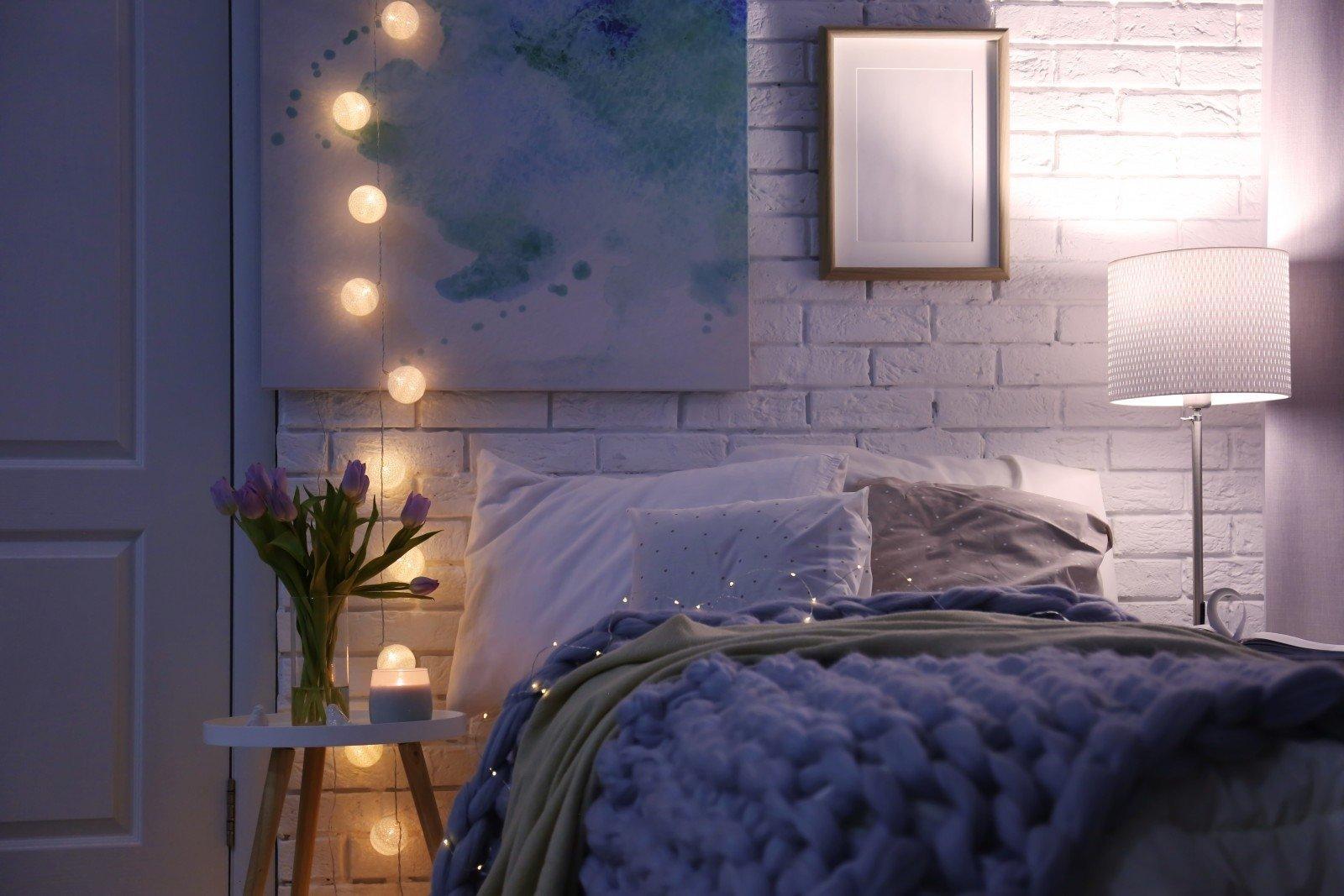 Przytulna sypialnia w bieli. Na pierwszym planie pościelone łóżko. Po bokach: biała lampa stojąca i świetlne kule.